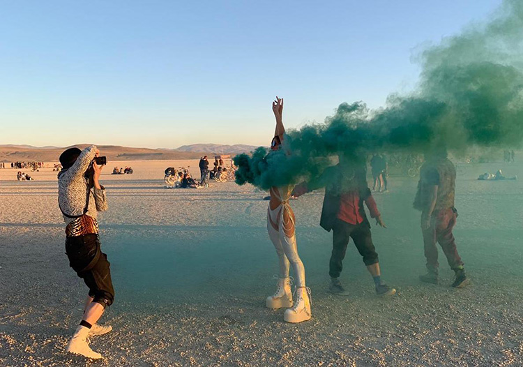 Woman with a smoke bomb in the desert at Burning Man